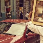 A image of a car with a red car in it and a shop and a man carrying a portrait