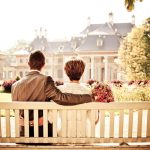 A couple sitting on a bench in a garden looking at a house