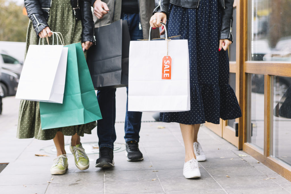 People walking down the street with shopping bags after a sale