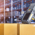 barcode scanner on boxes in stocked warehouse