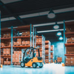 nterior of a storage warehouse with shelves full of goods and forklifts in action.