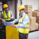 Warehouse manager and warehouse worker looking at a clipboard.