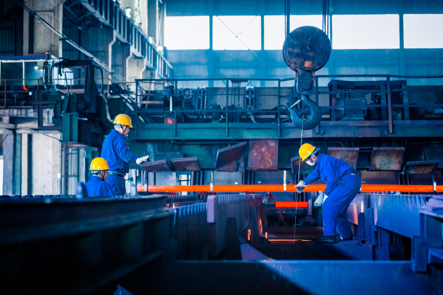 Photo of workers in hard hats and overalls working in a manufacturing warehouse. Used as a feature image for manufacturing software solution blog.