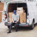 Delivery man without logistics management software solution manually filling out clipboard while sat in his van next to delivery boxes.
