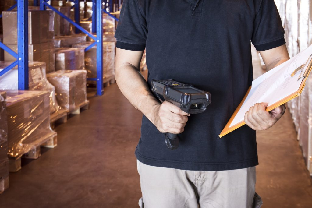Inventory management worker holding barcode scanner scanning an item in warehouse