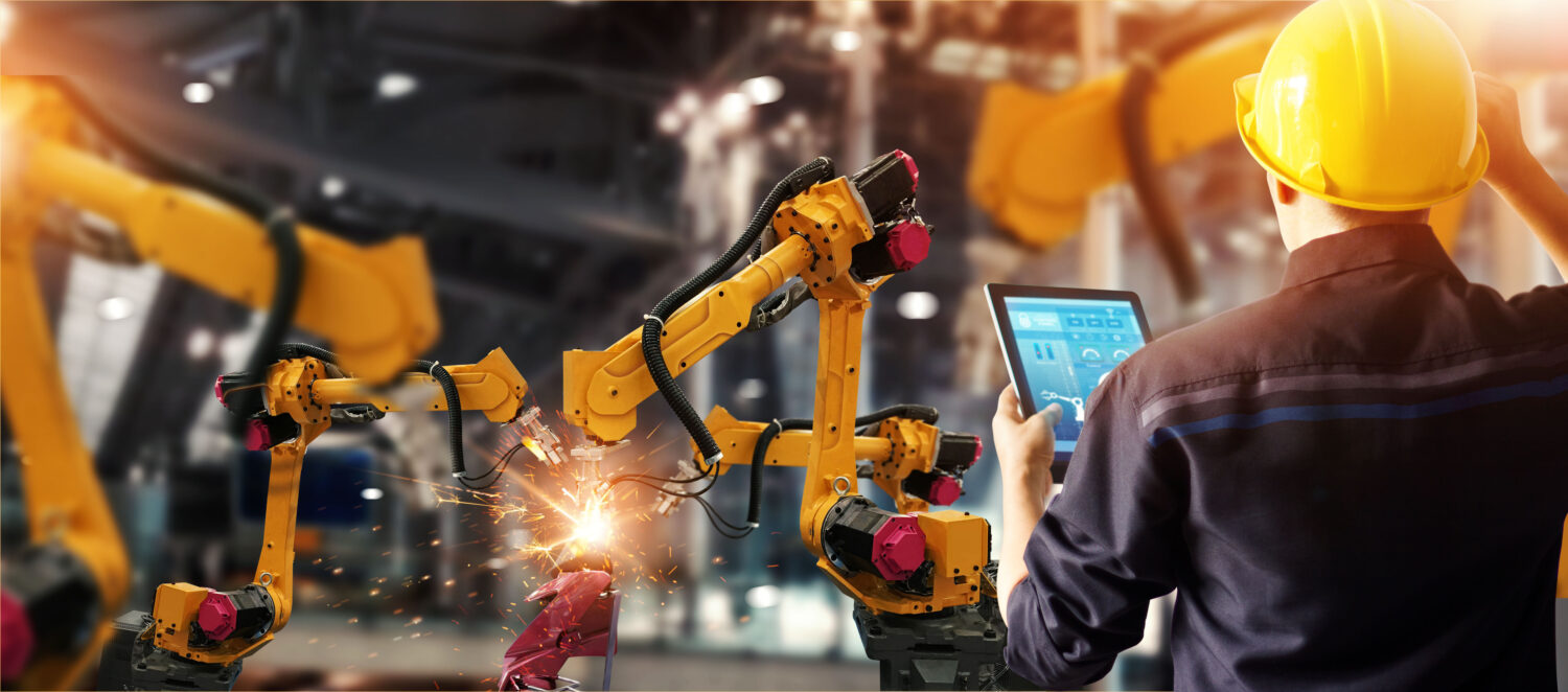 Engineer checking manufacturing software solutions and control welding robotics automatic arms machine in intelligent factory automotive industrial with monitoring system software. Digital manufacturing operation. Industry 4.0