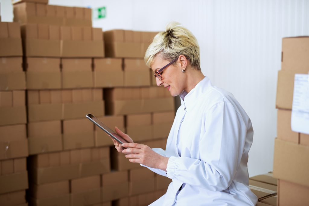 Satisfied female worker in sterile clothes is looking at tablet in storage room.