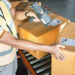 Man in a warehouse using a hand-held scanner scanning inventory